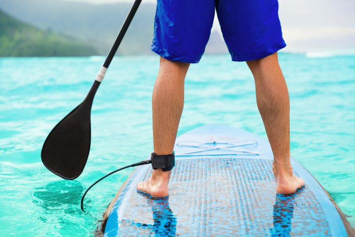 Paddle board man doing stand-up paddleboard on ocean